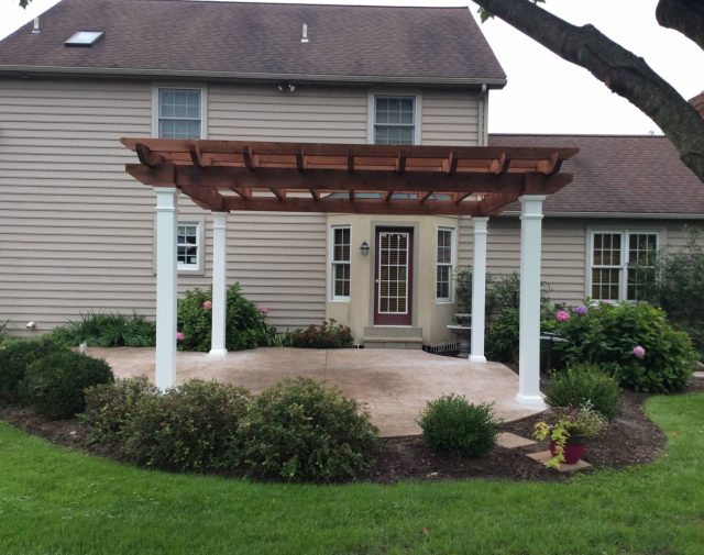 A dark stained cedar Timber Oasis pergola with white vinyl posts